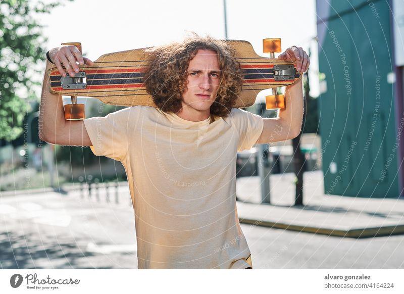 junger Mann mit lockigem Haar, der mit seinem Longboard oder Skeateboard auf den Schultern mitten auf der Straße in die Kamera schaut che Skateboard attraktiv