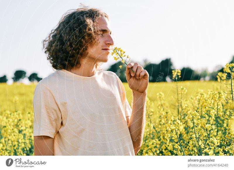 junger Mann mit lockigem Haar mit einer Blume in der Nase in einem Rapsfeld an einem sonnigen Frühlingstag gelb Natur Landschaft che männlich Porträt Typ
