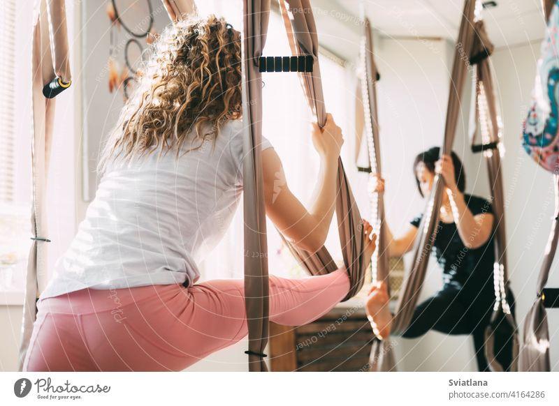 Ein Mädchen mit lockigem Haar praktiziert Yoga mit einer Hängematte. Yoga, Aero Yoga, Fitness, Lifestyle. Rückansicht Antenne Frau jung Antigravitation Asana