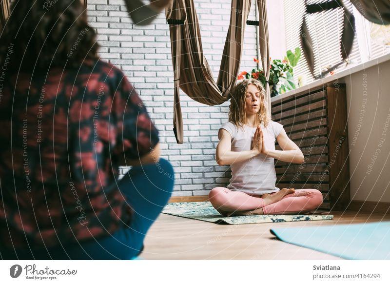 Zwei Frauen sitzen in einer Yogastunde auf einer Matte und meditieren nach einem Workout. Ruhe, Entspannung, Meditation Unterlage Pose Fitnessstudio sportlich