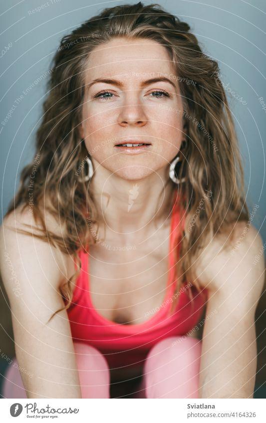 Porträt eines schönen Mädchens mit lockigem Haar in Sportkleidung auf einem grauen Hintergrund Yoga Sportbekleidung im Innenbereich praktizieren Atelier Lächeln