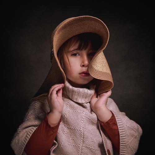 4 Jahre altes kaukasisches Mädchen mit Hut und einem Stoffponcho. Sie posiert stilvoll und elegant und hält den Hut mit ihren Händen. quadratisches Format