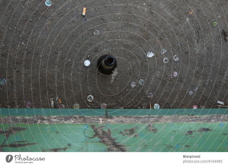 Leere Bierflasche, Kronkorken und Zigarettenkippen vor einer Bank in einer Grünanlage Flasche Parkbank Kronenkorken Kippen trinken rauchen draußen outdoor