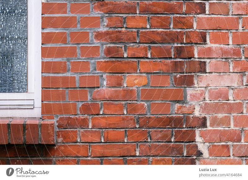 Teil einer Backsteinwand mit angeschnittenem Fenstersims und Fenster. Die unterschiedlich gefärbten Steine bilden ein geheimnisvolles Muster. Architektur rot