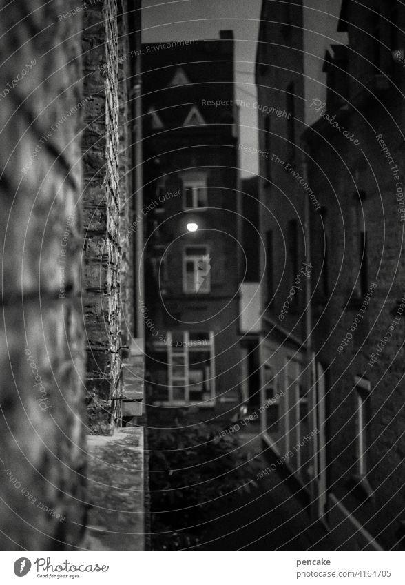 zwischenräume   mauern und wände. zwischen zwei fenstern ein licht. dunkel die gasse. Hauserfluchten schwarz-weiß Lahnstein Lampenlicht Zwischenräume Backstein