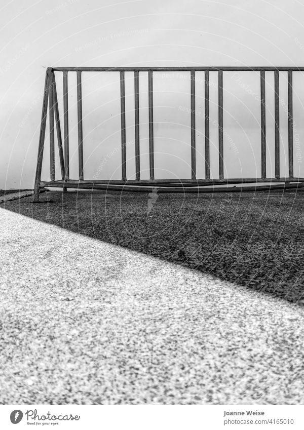 Fahrradständer aus Metall mit Schatten. Schwarzweißfoto Außenaufnahme Menschenleer grobkörnig Nachmittagssonne Tag Fahrradfahren Verkehr Textfreiraum unten alt