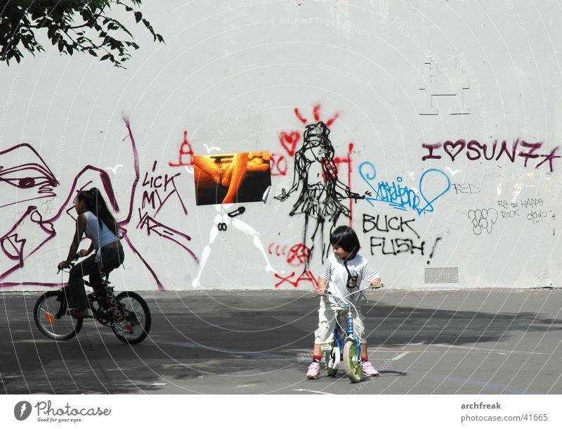 Phantasien in der Stadt Kind Mädchen Fahrrad Platz Wand Frau Mensch Tretroller Graffiti Fahrradfahren Spielen spielend Außenaufnahme