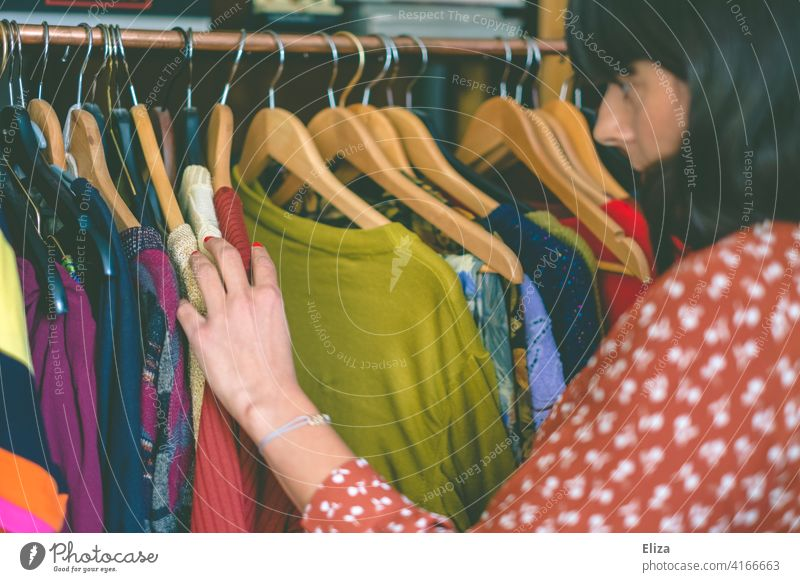 Junge Frau stöbert durch Klamotten auf einer Kleiderstange im Second Hand Laden oder auf dem Flohmarkt. Kleidung stöbern Anziehsachen bunt shopping