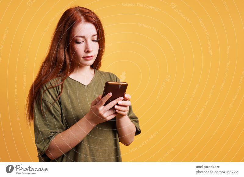 Junge Frau liest Textnachricht auf Smartphone oder Handy Nachricht lesen Texten SMS soziale Netzwerke Telefon Mädchen benutzend ernst Kaukasier lässig