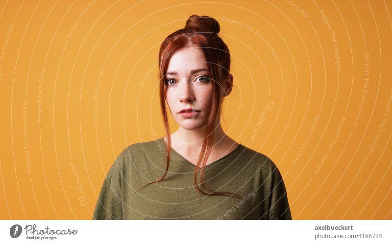 Porträt einer hübschen jungen Frau mit rotem Haar Dutt Junge Frau rothaarig Mädchen Vorhangpony Haarknoten Rotschopf Erwachsener schön ernst Gesicht Model