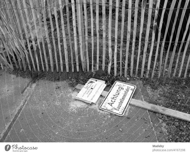 Umgestürztes Schild an einer Baustelleneinfahrt vor einem Holzzaun am Hafengarten in Offenbach am Main in Hessen, fotografiert in klassischem Schwarzweiß