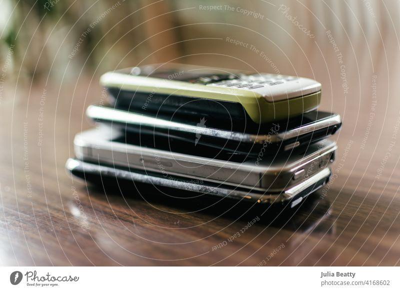 Stapel von vier alten Handys auf einem Esszimmertisch; das oberste Telefon ist grün Funktelefon veraltet Zelle Halt Mobile Drahtlos wiederverwerten e-cycle Müll