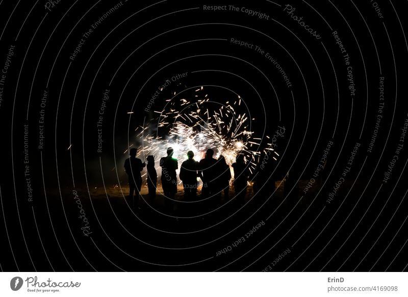Gruppe von Menschen in Silhouette beobachten Feuerwerk Nahaufnahme am Strand Nacht Licht Explosion glühen farbenfroh explodieren Feier Party Silvester 4. Juli
