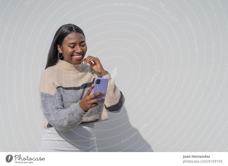 Junge schwarze Frau mit einem lila Smartphone hübsch jung Afrikanisch Funktelefon Afro-Look Afroamerikaner junger Erwachsener Handy Nachricht Internet