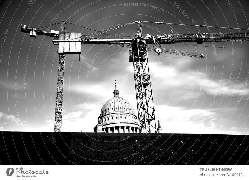 Ein Bau-Kran und noch ein Bau-Kran hinter einer dunklen Sichtschutz Wand bilden den Rahmen um den runden Turm der Nikolai Kirche, einem Wahrzeichen von Potsdam, vor leicht bewöktem Himmel