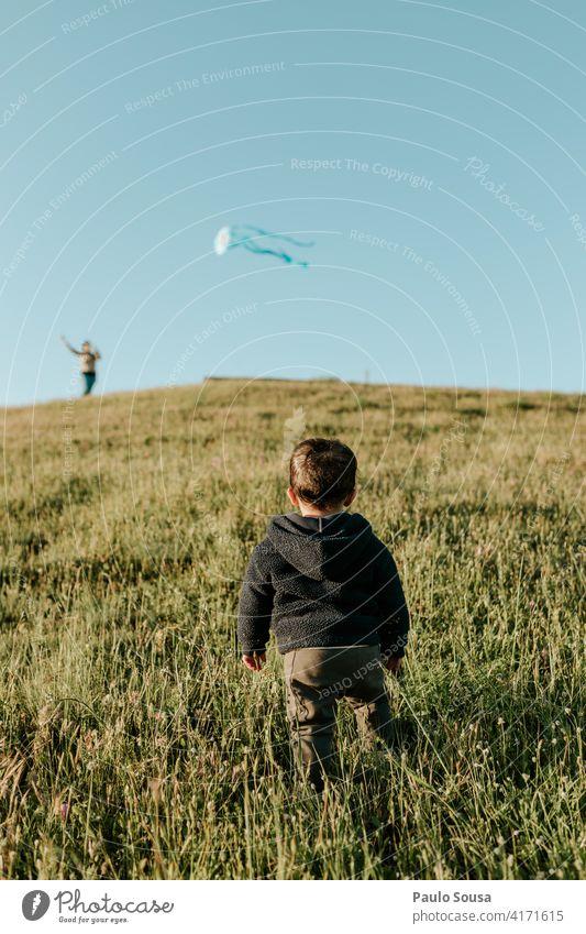 Rückansicht Kind schaut auf Kite Milan 1-3 Jahre Spielen Junge Kindheit Mensch Kleinkind Farbfoto Freude Fröhlichkeit Freizeit & Hobby Natur Leben Außenaufnahme