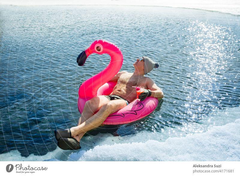 Ein Mann, der im Winter in Finnland in einem Eisloch schwimmt, schwebt auf einem rosa aufblasbaren Flamingo mit einem Cocktail in der Hand. Urlaubsoptionen, die vom Sommer träumen.