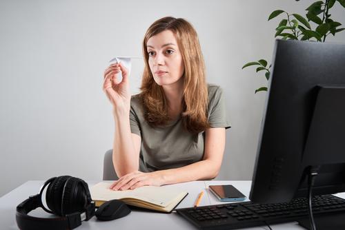 Frau hält Papierflugzeug bei der Arbeit im Büro zu Hause prokrastinieren freiberuflich online heimwärts LAZY Business Arbeitsbereich Computer Unternehmen