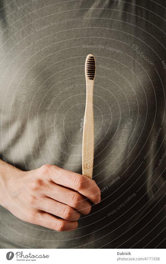Frau hält Bambuszahnbürste, Nahaufnahme Zahnbürste Öko Pflege Hygiene wiederverwendbar umweltfreundlich keine Verschwendung Gesundheit Sauberkeit Reinigen