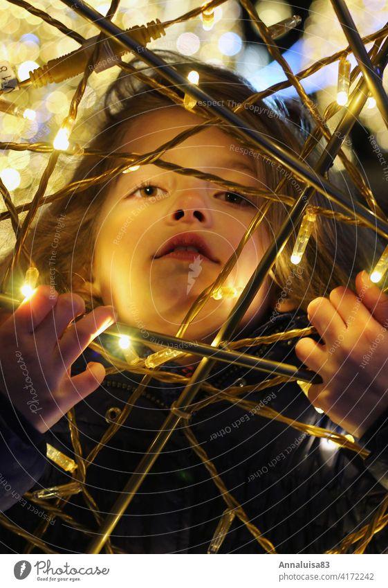 Gefangen im Licht Kind Mädchen Porträt Winter Gesicht gefangen leuchten LED Lichterkette Weihnachten & Advent Weihnachtsmarkt winterjacke kalt bunt Abend Nacht