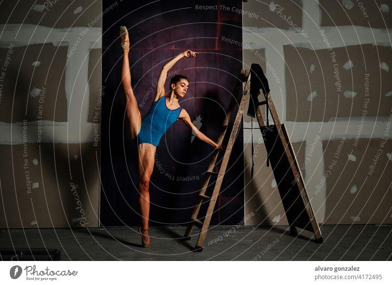 junge Balletttänzerin im Studio Leistung Tänzer Frau Flexibilität Tanzen Weiblichkeit strecken Split zierlich theatralisch professionell Ballerina Künstlerin