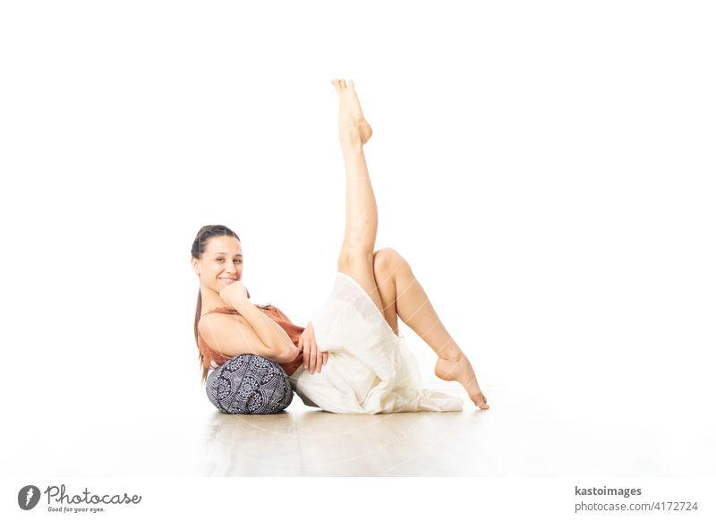 Restorative Yoga mit einem Bolster. Junge, sportliche Yogalehrerin in einem hellen, weißen Yogastudio, auf einem Kissen liegend, sich streckend, lächelnd, Liebe und Leidenschaft für restauratives Yoga zeigend