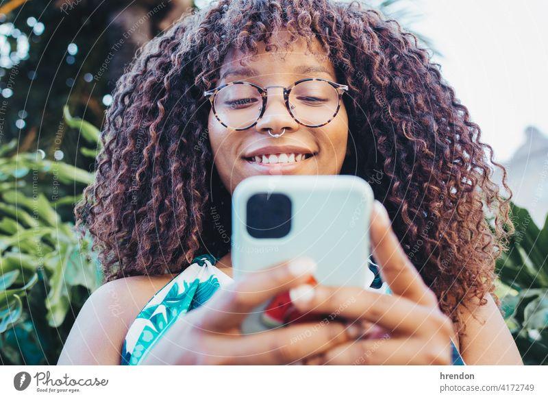 Nahaufnahme eines afrikanischen Mädchens mit ihrem Smartphone Frau Afrikanisch Telefon Behaarung Gesicht Mitteilung jung Technik & Technologie schwarz