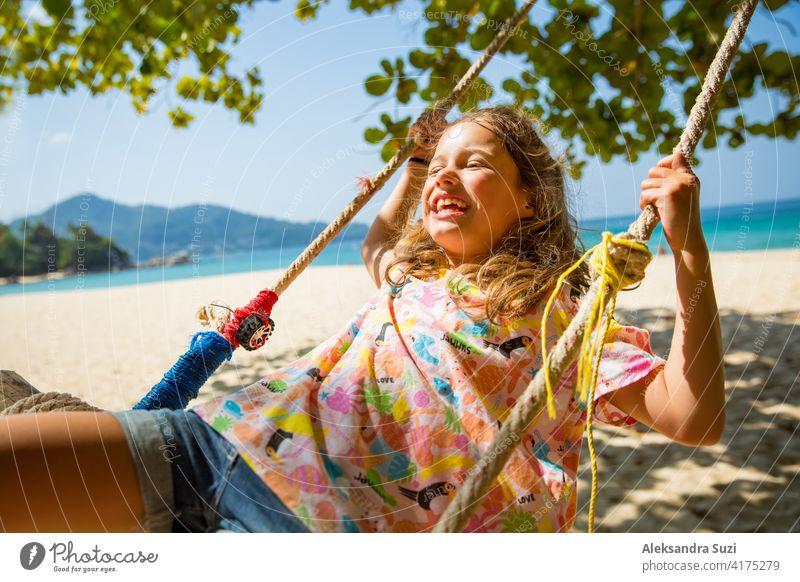 Glückliche niedliche kleine Mädchen lachen und schwingen auf Schaukel auf dem Baum am Strand. Schöne Sommer sonnigen Tag, türkisfarbenes Meer, Felsen, weißer Sand, malerische tropische Landschaft. Phuket, Thailand. Unbeschwert