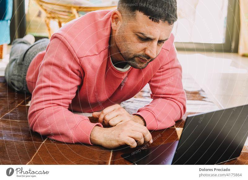 Mann arbeitet wegen der Coronavirus-Pandemie mit seinem Computer auf einem Teppich im Wohnzimmer Schreibmaschine Pijama Kaukasier männlich Person Menschen