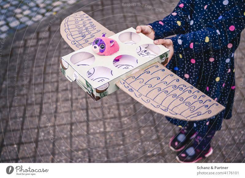 selbstgebasteltes Kuscheltierflugzeug basteln Kind pielen fantasie Flugzeug fliegen Urlaub Kucheltier selbermachen Flügel Pappkarton upcycling bemalt Stofftier