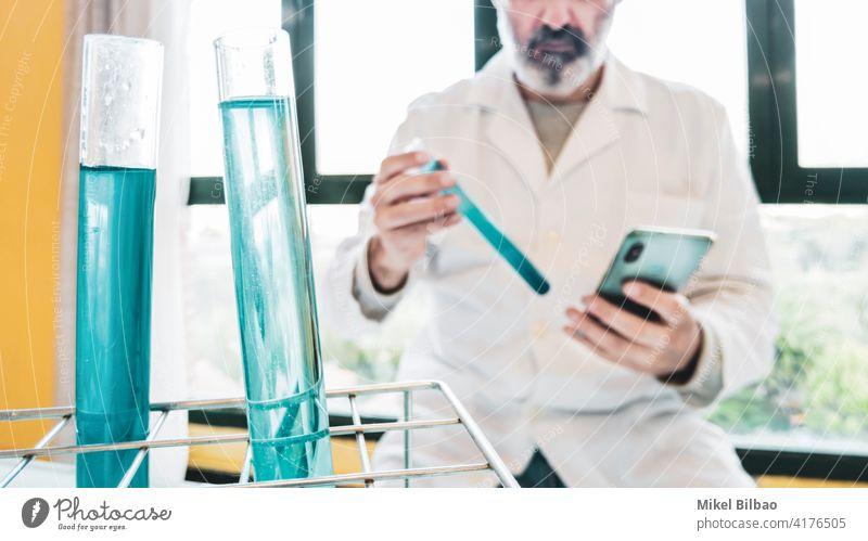 Reagenzgläser mit Flüssigkeit und Wissenschaftler mit Laborkittel und einem Mobiltelefon in einem wissenschaftlichen Labor.  Wissenschaftliches Konzept. Prüfung