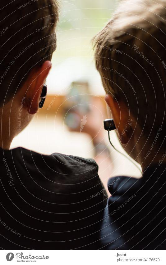 Zwei Jugendliche streamen gemeinsam Musik über das Handy jugend jugendlicher streaming hören Kopfhörer Musik hören ear Ohren Ohrenstöpsel sehen Smartphone smart