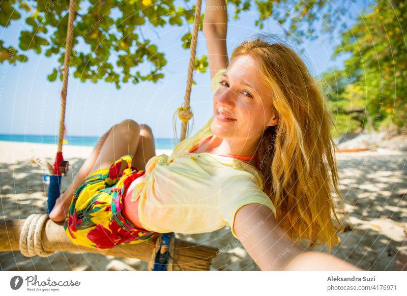 Glückliche junge Frau mit roten Haaren lachen und schwingen auf Schaukel auf einem Baum am Strand, ein Selfie zu nehmen. Schöne Sommer sonnigen Tag, türkisfarbenes Meer, weißer Sand, tropische Landschaft. Phuket, Thailand.