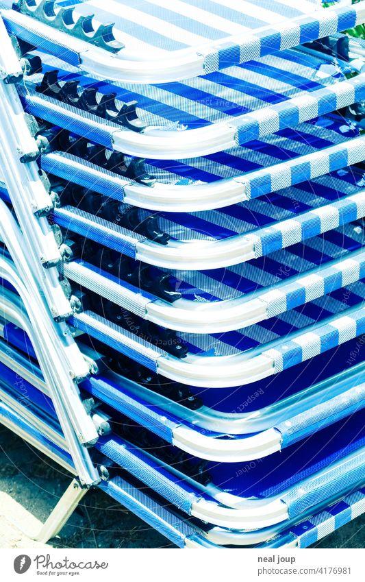 Detail eines Stapel von blau weißen Sonnenliegen im gleißenden Sonnenlicht Urlaub Sommer hell Griechenland glänzend Stahl Metall Textil Ferien & Urlaub & Reisen