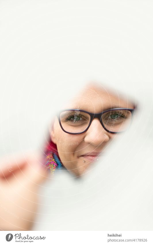 Frau schaut freundlich durch eine Spiegelscherbe in die Kamera feminin Junge Frau Mensch Erwachsene 18-30 Jahre Porträt Gesicht Kopf Spiegelung Brille Blick