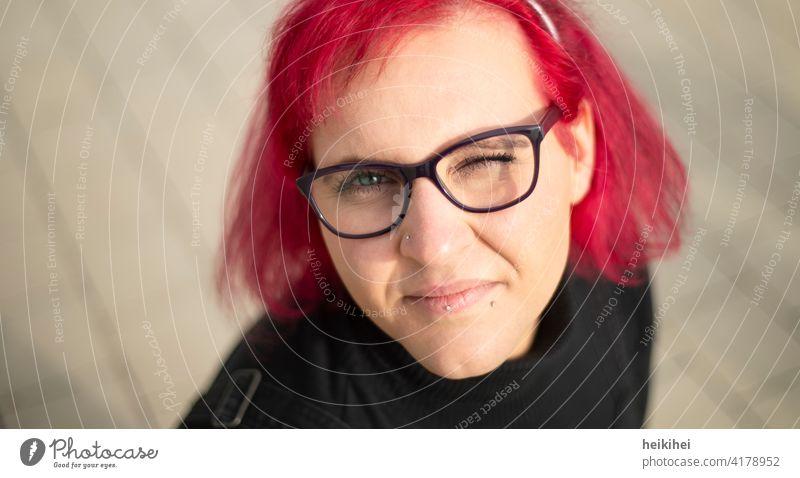 Eine rothaarige Frau mit Brille und Piercings schaut zwinkernd in die Kamera frau brille portrait lippenpiercing auffallend erscheinungsbild ausstrahlung jung