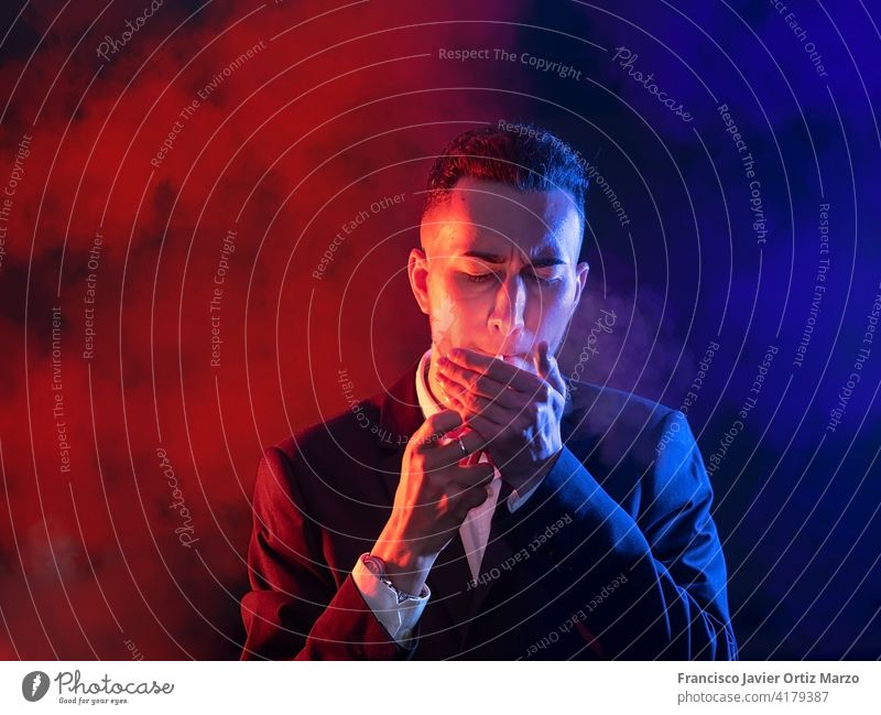 Eleganter junger Mann beim Anzünden einer Zigarre auf schwarzem Hintergrund. Selektiver Fokus Textfreiraum elegant Kaukasier Model Typ ernst Manager Ausdruck