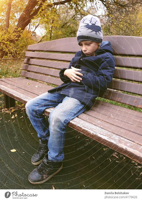 trauriger Junge sitzt auf Bank allein im Freien hoffnungslos Erinnern an nachdenklich negativ Fehler beunruhigt verzagt Jugendlicher gutaussehend Bildung