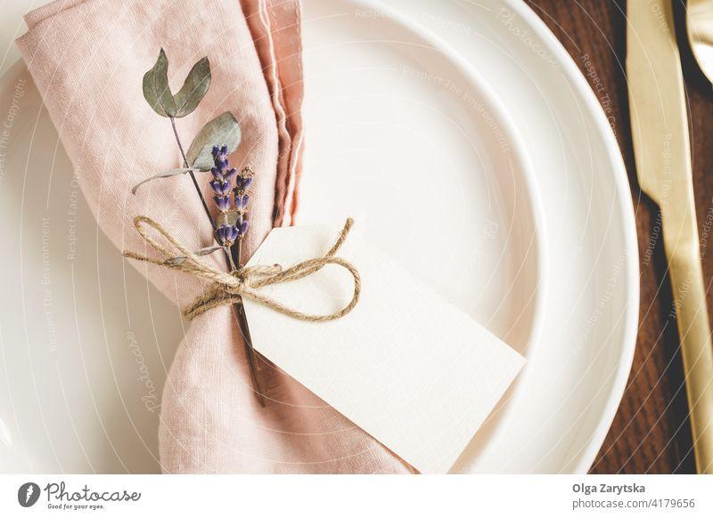 Details zur Tischgestaltung auf weißen Tellern. Tabelleneinstellung Detailaufnahme Serviette rosa Leinen geblümt Tag blanko Lavendel abschließen golden Besteck