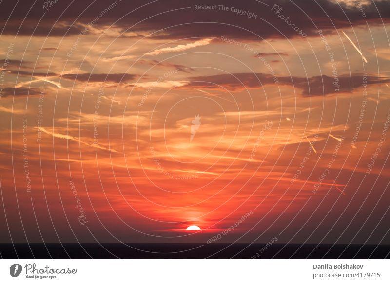 schöner Blick auf die Sonne, die sich hinter der Meeresoberfläche versteckt. Der Himmel ist bei Sonnenuntergang orange mit Wolken und Kondensationsspuren
