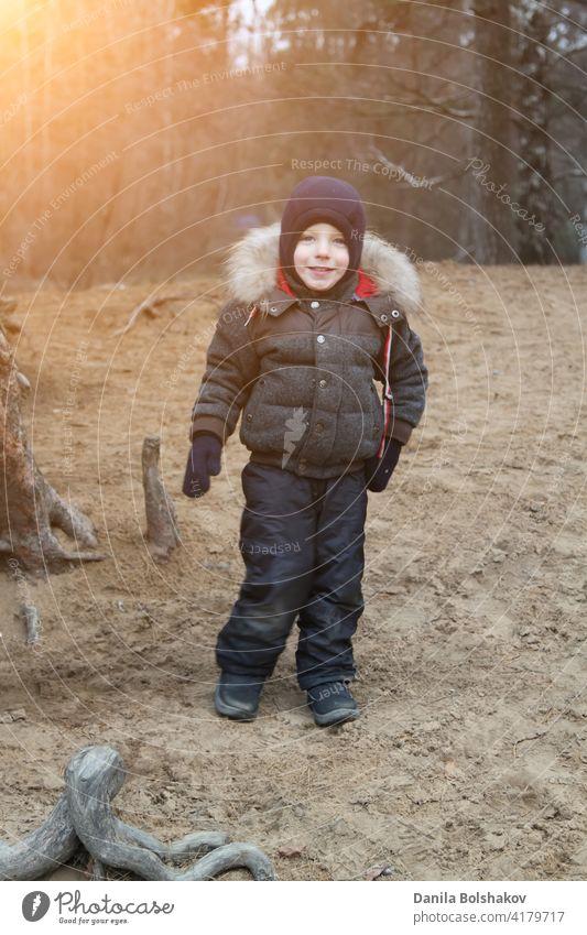 glücklich lächelnden Jungen in warmer Kleidung und Hut bedeckt seinen Hals vor kaltem Wind llooking at Kamera im Herbst im Freien Zähne Smiley Mantel blau