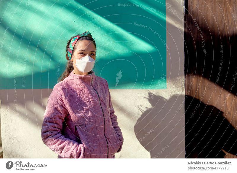 Porträt der jungen Frau mit schützenden Gesichtsmaske Blick in die Kamera. Trägt handgemachte rosa Jacke. Türkisfarbene Wand auf dem Hintergrund. Junge Frau