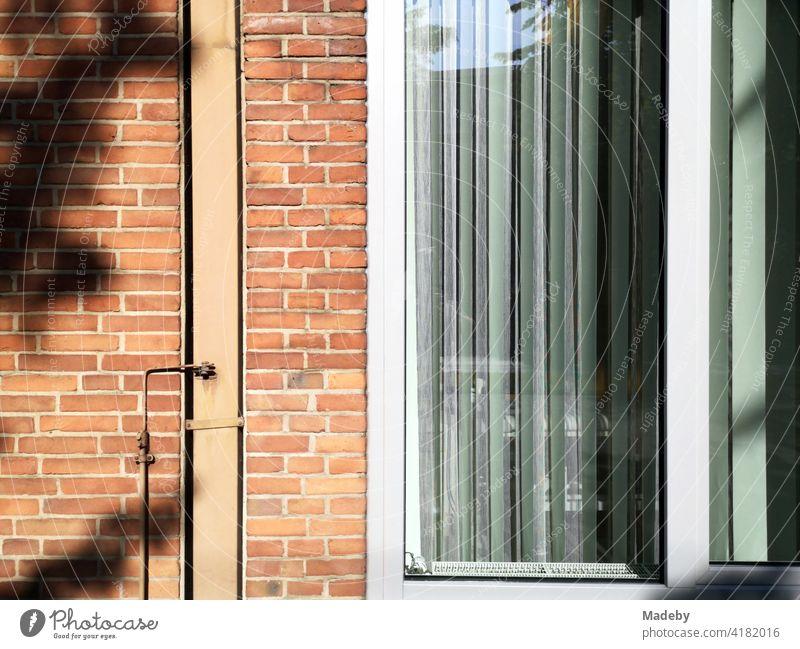 Backsteinfassade mit großem Fenster und Lamellen als Sonnenschutz bei Sonnenschein in Bielefeld im Teutoburger Wald in Ostwestfalen-Lippe Fassade Klinker