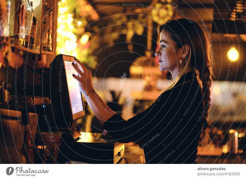 eine schöne junge Frau an der Rezeption in einem Restaurant Stehen Schreibtisch berührend Kasse bezahlen Manage Bar Lifestyle Touchscreen benutzend Rechnung