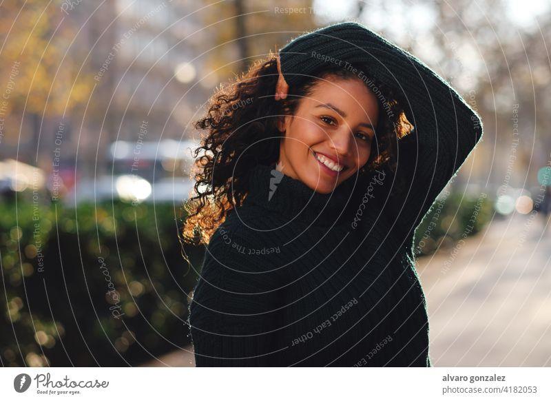 Frau lächelnd beim Posieren im Freien. jung urban Straße Sombrero posierend Stil Großstadt Nahaufnahme lockig Behaarung Frisur Bekleidung trendy eine Pose