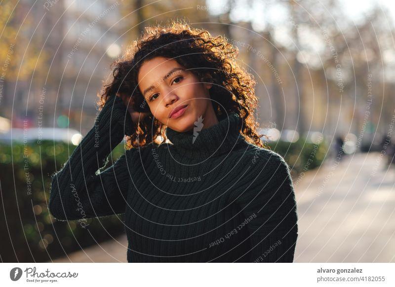 Junge Frau steht im Freien auf der Straße. jung urban Sombrero Stehen Stil Großstadt Nahaufnahme lockig Behaarung Frisur warm Bekleidung trendy eine posierend