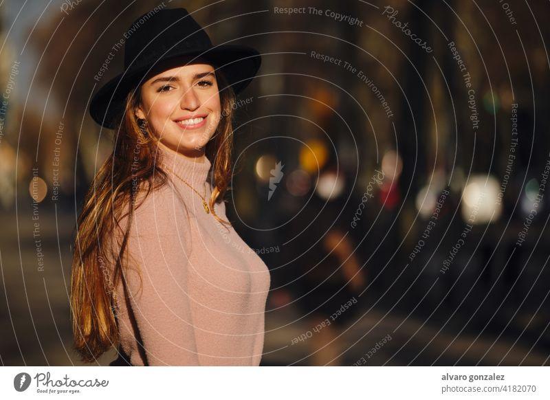 Frau lächelt, während sie im Freien steht. urban Straße Sombrero Großstadt Stehen Stil jung Nahaufnahme Pullover Bekleidung außerhalb eine posierend