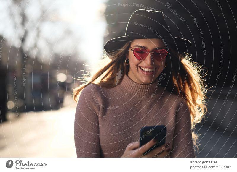 Junge Frau benutzt ihr Mobiltelefon im Freien. Mobile Telefon urban Smartphone sozial Medien Sombrero Mitteilung Sonnenbrille Funktelefon eine selbstbewusst