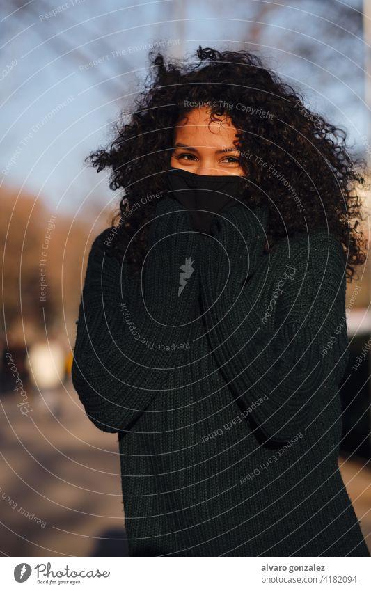 Frau mit Gesichtsmaske beim Stehen im Freien. Mundschutz urban Straße covid-19 Sombrero Stil Großstadt Nahaufnahme lockig Behaarung warm Bekleidung Pandemie