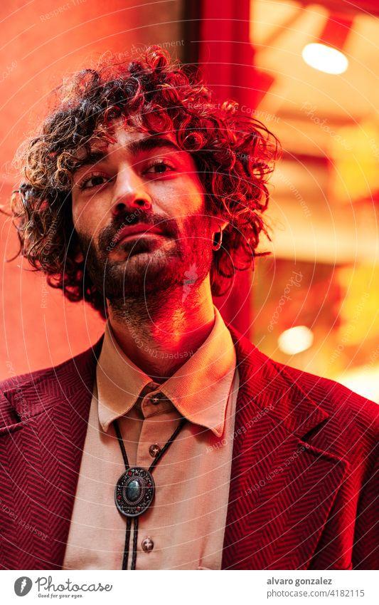 junger kaukasischer Mann in der Nähe eines Neonlichts mit blauen und roten Lichtern neonfarbig männlich Model Erwachsener Menschen Person Porträt Typ Gesicht